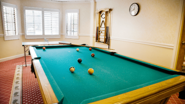 a billiards room with a green pool table
