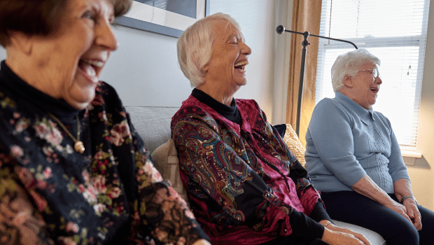 three residents sharing a laugh in the lounge