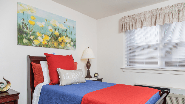 nice bedroom with a large blue and red bed and a window