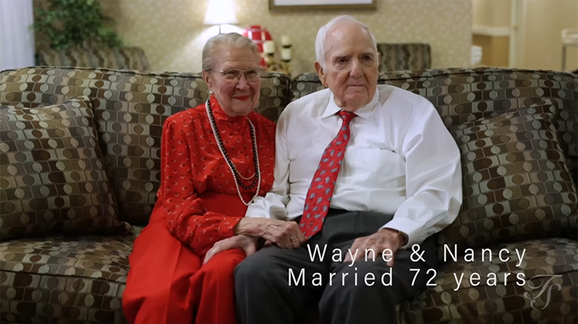 Senior couple seated on a couch and holding hands