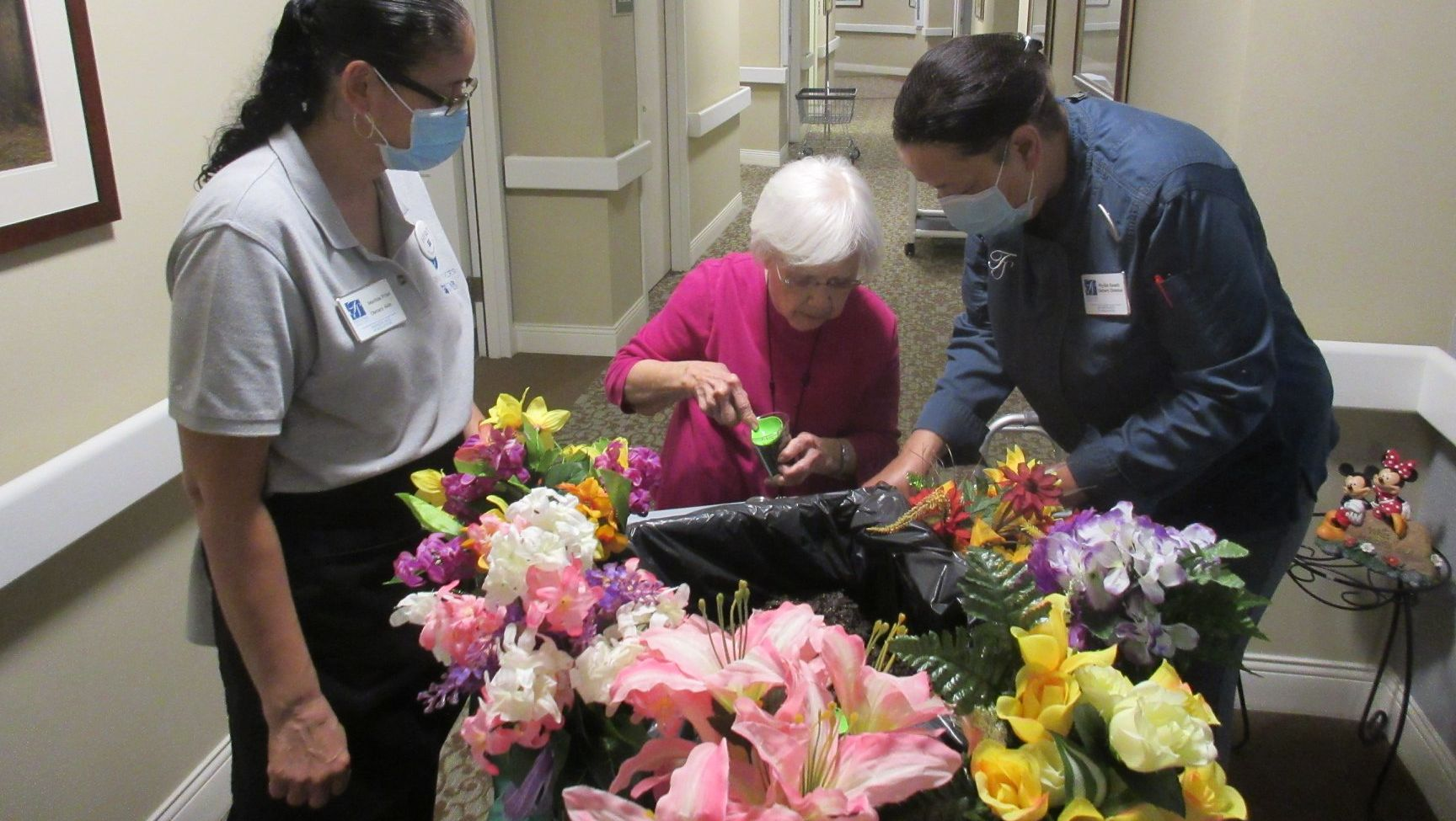 a resident and some employees with flowers