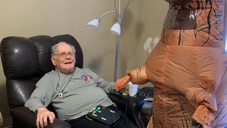 a happy resident with the t-rex mascot