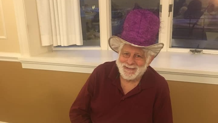 a happy resident wearing a large purple hat