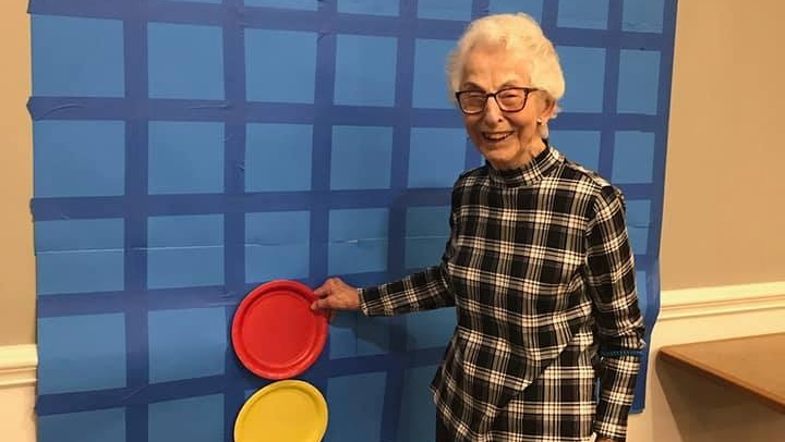 a resident having fun playing large-size connect four