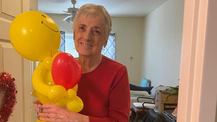a very happy resident with a balloon