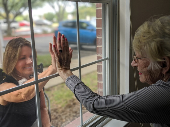 resident and daughter talking through window